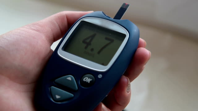 Woman hand with glucometer displaying normal blood sugar range video