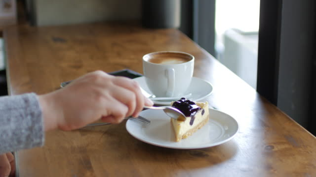 Woman Hands Cutting blueberry cheese pie with coffee at relax time , coffee cafe , dolly shot video