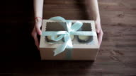 Woman hands giving gifts. Present made of recycled carton and  ribbon video
