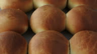 Woman hands open a warm and fresh bread roll. Food background copy space video