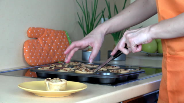 woman hands take out baked meat cup cakes from cookie sheet and put in dish video