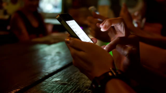 woman hands using smart phones at the bar video