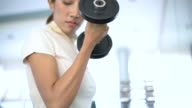 Woman hands weight with a dumbbell in health club video