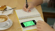 Woman hands writing in notebook at coffee cafe with coffee , cake and smartphone , 4k(UHD) video