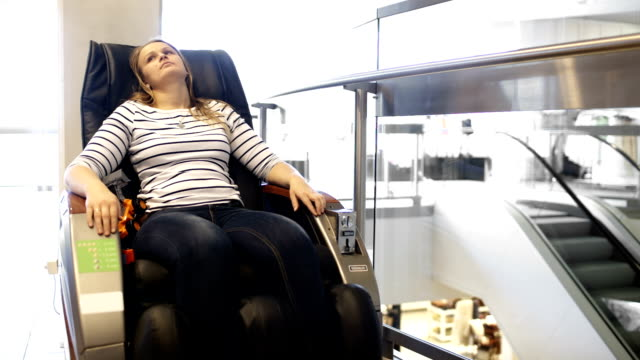 Woman having a rest in massage chair shopping center video