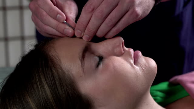 Woman having Acupuncture done on her face video