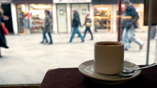 Woman having coffee by the window in cafe video