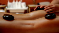 Woman having her legs massaged with hot stones in spa video