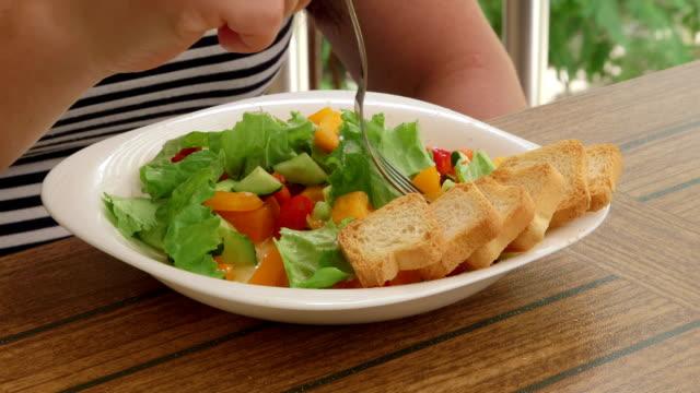 Woman having outside light lunch on the balcony eating fresh vegetable salad video