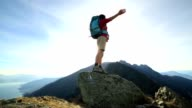 Woman hiker arms outstretched on mountain ridge crest video