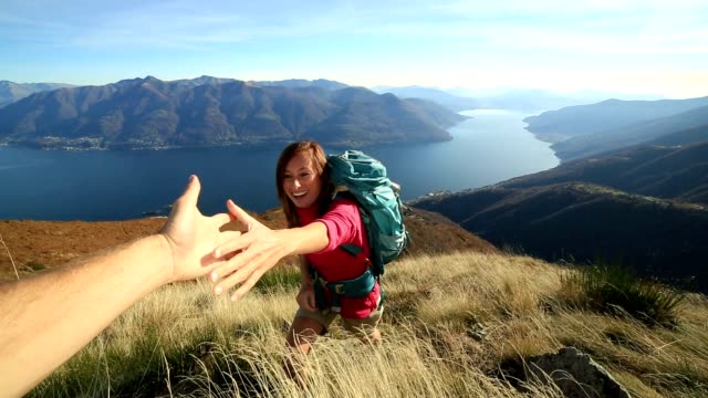 Woman hiker climbing mountain, hand reaches out to help video