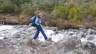 Woman hiker crossing a frozen stream video