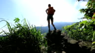 woman hiker enjoy the view at mountain peak cliff video