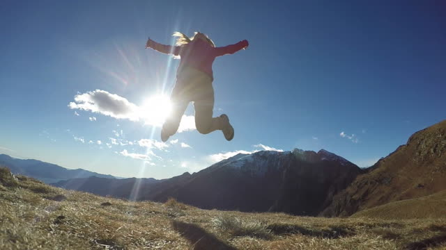 Woman hiker jumping in slow motion from mountain top video