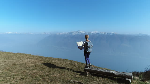 Woman hiker reaches mountain top, looks at map video