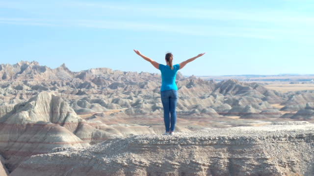 Woman hiker standing on top of mountain in Badlands with arms raised towards sky video