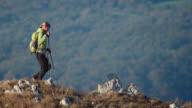 Woman hiker walking down the mountain video