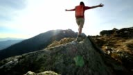 Woman hiker walking on mountain ridge crest video