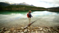 Woman hiker walks on log arms outstretched video