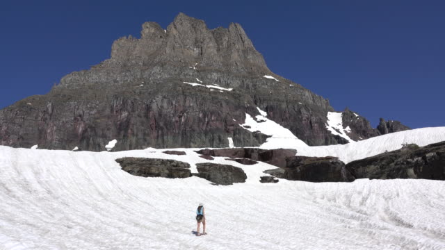 Woman hikes Glacier National Park Logan Pass snowfield Clements Mountain Montana video