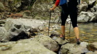 Woman hiking and crossing mountain stream video