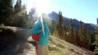 Woman hiking on trail stops to admire landscape video
