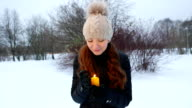 Woman hold yellow candle, protect it from wind by palm, look at camera video