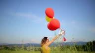 Woman holding baloons outdoors video