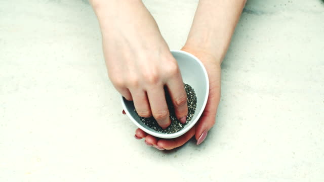 Woman Holding Bowl Of Chia Seeds At Counter video