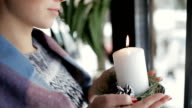 Woman holding burning candle at window in cafe - cropped shot video