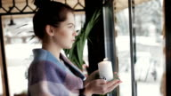 Woman holding burning candle at window in cafe video