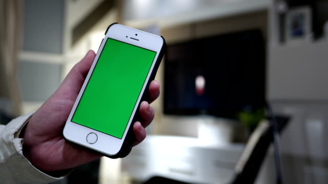 Woman holding green screen phone with blurry living room video