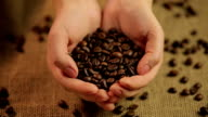 Woman holding handful of flavorful roasted coffee beans, world's favorite video