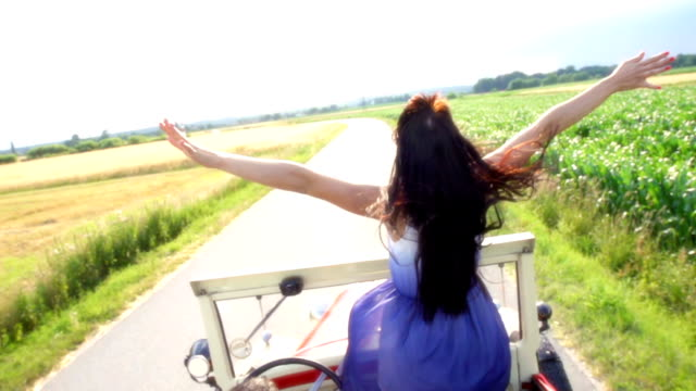 HD SUPER SLOW-MOTION: Woman Holding Her Arms Up In Convertible video