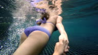 Woman holding man's hand and leading him under the water in swimming pool video