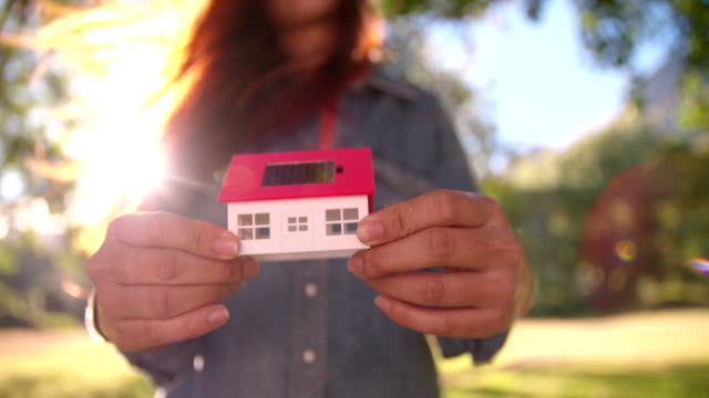 Woman holding model of new home on a sunny lawn video