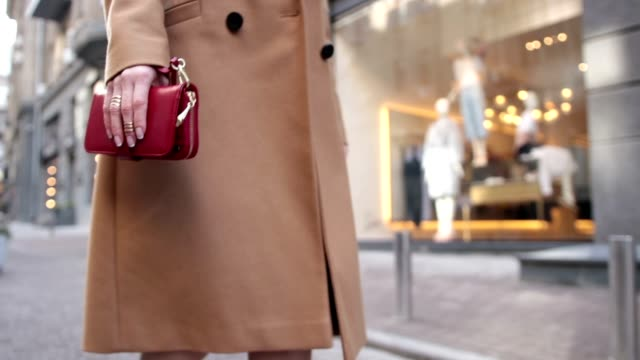 Woman holding red clutch while walking on street video