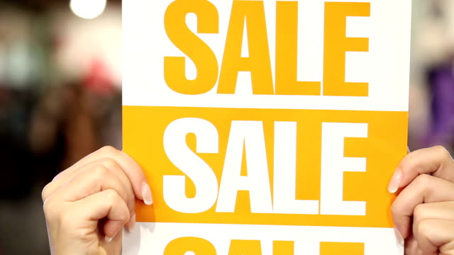 Woman holding sale sign video