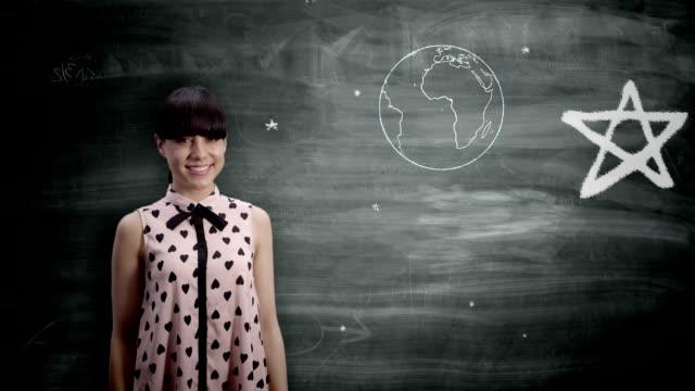 Woman holding the Earth on a blackboard video