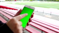 Woman holds a blank smart device with a green screen for your own custom content at sport filed video