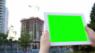 Woman holds a blank tablet PC with a green screen for your own custom content. video