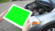 woman holds blank tablet PC with green screen video