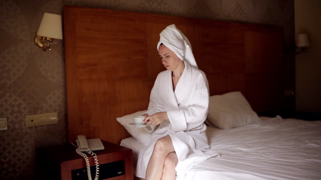 A woman in a bathrobe after a shower drinks coffee and phone calls to the reception desk video
