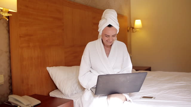 Woman in a bathrobe. Young pretty woman in bathrobe drinking coffee and looking in the window while sitting on bed video