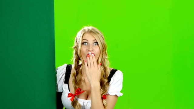 Woman in a bavarian costume shows thumb. Oktoberfest. Green screen video