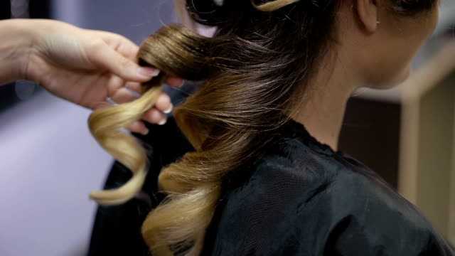 Woman in a beauty salon. hairstyles wizard makes client curls video