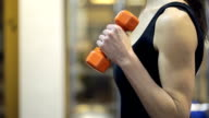 A woman in a black vest pumps hands with orange dumbbell in the gym video