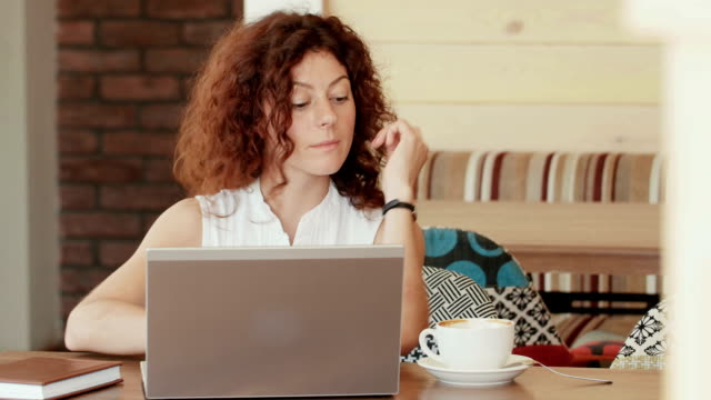 woman in a cafe , drinking coffee and working on the laptop . video