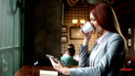 Woman in a cafe using tablet and drink coffee video