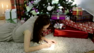 A woman in a gray dress writes a letter to Santa. video